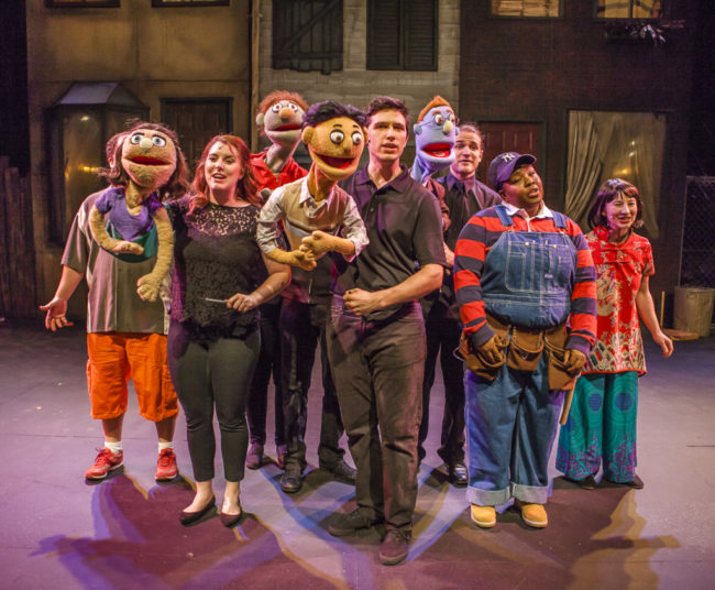 Josh Scoff (center) as Princeton with the Company of Avenue Q at Cockpit in Court