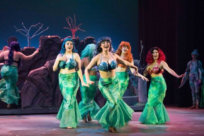 Malarie Zeeks (center) as Arista and The Mersisters (surrounding) Ellen Manuel as Aquata, Elisabeth Johnson as Andrina, Kaitlyn Jones as Atina, Emily Caplan as Adella, and Hannah Bartlett as Allana in The Little Mermaid