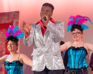 Hosea Mundi (center) as Buddy Rocky and the Showgirls of Honeymoon in Vegas