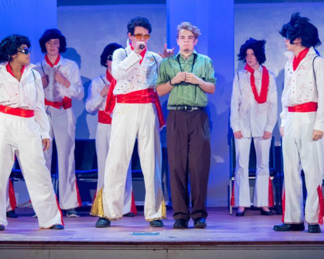 Henry O'Toole (center left) as Roy Bacon and Nick Zuelsdorf (center right) as Jack Singer and the ensemble of Honeymoon in Vegas