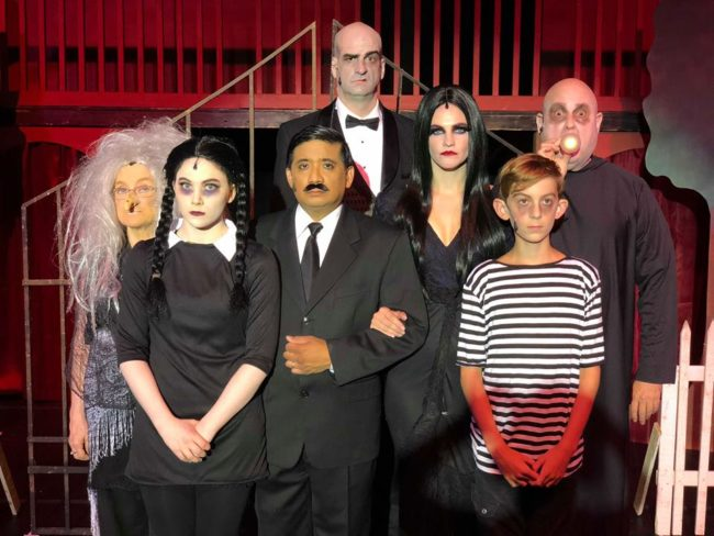 "They're creepy and they're kooky, mysterious and spooky – and in this case, they're altogether entertaining! The Addams Family (created by author Charles Addams,) a somewhat unusual clan who were introduced in a comic strip, segued into television in the 1960's and onto movie screens in the 1990's have now made their way onto the stage in musical form – and they are just as outrageous as ever. With a stellar cast and brilliant direction by Jonathan C. Jackson, the Tantallon Community Players are bringing highly-energized, Broadway-caliber performances of this 2010 comedy to the Harmony Hall Regional Center in Fort Washington, MD – and from the abundance of laughing, whistling, and cheering heard in the house on opening night, audiences aren't going to be able to get enough of the quirky tribe – or this phenomenal production. For those not familiar, the Addamses are like any other family… except… not. They prefer the shadier side of life – the more macabre and torturous the better. Smooth-talking Gomez and darkly-sexy Morticia are parents to ""goth-before-goth-was-a-thing"" daughter Wednesday – and her brother/victim, Pugsley; the odd-but-loveable Uncle Fester – Gomez's brother – also lives with them, as does apothecary Grandma (though no-one remembers if she is actually related to anyone in the house.) Lurch, their butler, is an ominous figure of few words – well, let's be honest, he mostly grunts. Cousin Itt, who resembles a mop wearing a hat and glasses, makes a cameo appearance. Then there's the disembodied hand, called simply, ""Thing,"" who offers himself when needed (see what I did there?) Oh, yeah, there's also a group of ghostly Addams ancestors – visible to some, but not all – who lurk about the place randomly bursting into song and dance. Normally, everyone is perfectly unhappy with the status quo – and that is a good thing. However, on this particular occasion, Wednesday would like her family to be a little less like themselves. She's met a boy – a normal one – and she wants to marry him. But she's afraid that her family's… eccentricities, shall we say… might just scare Lucas and his family off. She wants the Addamses to act like ""regular"" people for once. The question is, are they really capable of that? From the very first moment the cast explodes onto the stage singing, ""When You're an Addams,"" it becomes clear you're in for a treat. The unbelievable spirit built up in the theater is palpable as you watch multiple generations of Addamses, both alive and undead, sing and dance to director Jackson's wonderfully fluid and sometimes amusingly familiar choreography (there *may* have been some ""Thriller"" moves thrown into the mix.) As patriarch Gomez Addams, Kieth Flores takes command of a role most famously played by John Astin in the television show and Raul Julia in the movies and easily makes it his own. It may be partially due to the excellent work of costumer Crystal Soul, multiple-hat-wearing Jackson's wig design, and/or skillful makeup application, but Flores – and truly, each member of the cast – looks like he was born to play his role. Patrick Boyer, in particular, could be the ancestor of Ted Cassidy, who played Lurch in the TV show.  Steve Dasbach is a very sweet and amiable Uncle Fester. When he announces that he's in love with the moon, you really want it to work out – even if she is a quarter of a million miles away (though he doesn't mind; he claims that's a good distance for romance.) Spunky Lani Novak takes on the role of Grandma Addams and makes it larger than life. The youngest member of the cast, Jackson Parlante, as Pugsley Addams, embodies the term, ""good things come in small packages."" Not only is he a wonderful actor, when he sings his solo, ""What If,"" it will bring you to tears.  Being on stage with such flamboyant characters can make it difficult for actors with more subdued roles to stand out, but Will Hooper, Libby Dasbach and George Willis as Wednesday's betrothed and his mother and father, respectively, are to be commended for their fine work in that regard. Dasbach, especially, is hilarious when she accidentally drinks one of Grandma's potions and really lets her hair down. The talented Nina Jankowicz plays Morticia Adams to sultry perfection and has one of the best singing voices in the cast. However, the true standout in this production is Jayne Saxon Zirkle as Wednesday Addams. Not only does she give her role a lot of layers (which can be difficult to do with a somewhat one-sided character like Wednesday,) she has a killer singing voice – strong, clear and full of emotion. She honestly blew me away. Every aspect of this production is well thought-out and brilliantly executed. There are a lot of small touches that make it special. For instance, at the very top of the show a (presumably battery-run) hand (the aforementioned Thing) rapidly and amusingly skitters across the stage, setting a whimsical tone for the rest of the evening. Lighting designer Levante Evans is to be commended for using spotlights as a masking device while sets are being changed in the background – and for making sure that each and every actor finds his or her light, even if the light has to find them.  So… what are you waiting for? Go see The Addams Family. What's the magic word, you ask? NOW. Running Time: Approximately 2 hours and 30 minutes with one intermission The Addams Family plays through September 30, 2018 with the Tantallon Community Players at The Harmony Hall Regional Center— 10701 Livingston Road in Fort Washington, MD. Tickets are available at the door or in advance online."