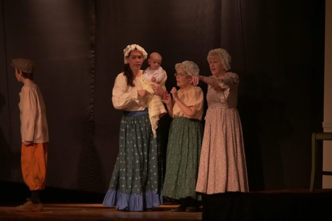 Kristy Wiggins (left) holding the youngest member of a St. Gabriel Miracle Players' production to ever appear on stage, Joshua Wiggins, at not-quite-six months old, as street ensemble members in Oliver!