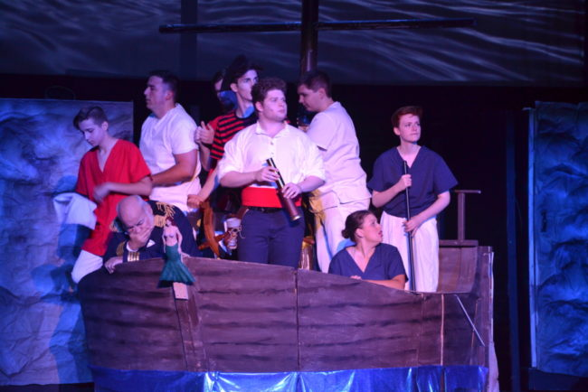 Nicholas Cloutier (center) as Prince Eric and the crew of his ship in The Little Mermaid